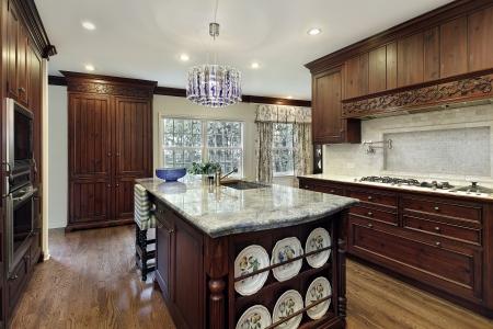 granite kitchen: Traditional kitchen with dark wood cabinetry and granite island Stock Photo