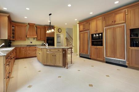 豪華なオーク材のキャビネットを持つ家で大きなキッチン