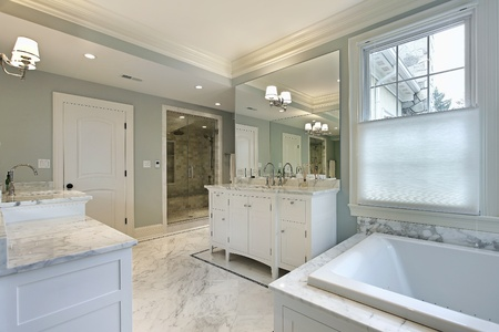 Large master bath in luxury home with white cabinetry photo