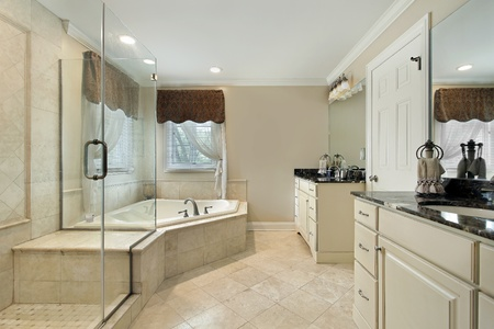 bathroom interior: Master bath with cream colored cabinetry and glass shower