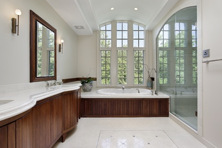 Master bath in luxury home with wood cabinetry photo