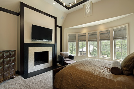 Master bedroom with fireplace and wall of windows photo