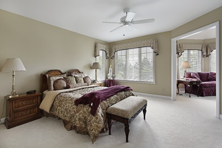 Master bedroom in luxury home with adjacent sitting room photo