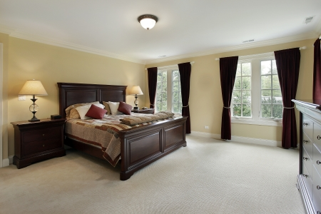 bedroom design: Master bedroom in luxury home with mahogany furniture Stock Photo