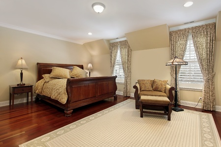 Master bedroom in luxury home with cherry wood flooring Stock Photo