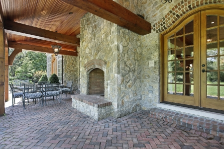 Brick patio outside luxury home with stone fireplace