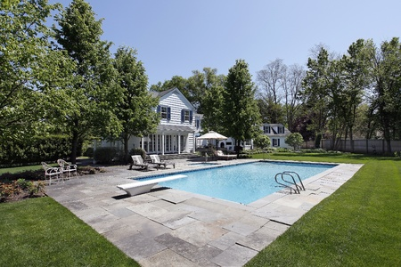 Swimming pool outside luxury home with diving board photo