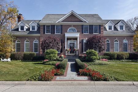 Luxe bakstenen huis met kolom in-en bloemen Stockfoto