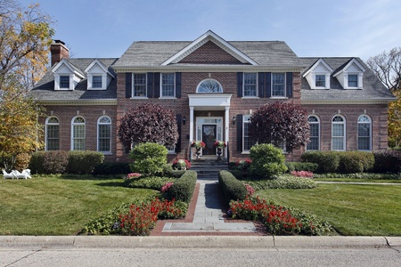 Luxury brick home with column entry and flowers photo