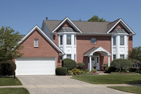garage: Brick home with columns and arched entry