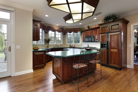 Kitchen with dark wood cabinets and green island counter Stock Photo