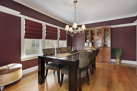 familia cenando: Comedor con paredes de color marr�n y tres ventanas