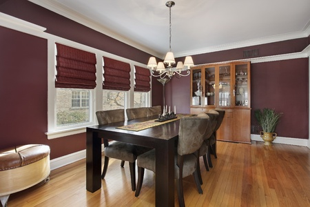 living room interior: Dining room with maroon walls and three windows