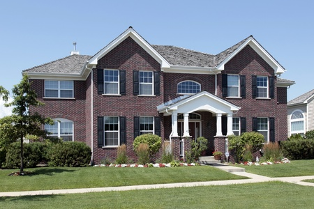 Large brick home with white arched entry Foto de archivo