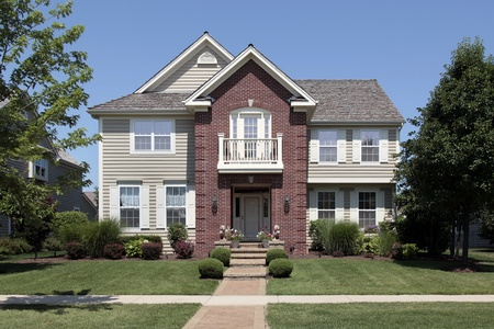 Brick home with beige siding and front balcony Stockfoto