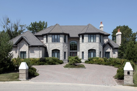 Large stone home with pillars and brick driveway Stockfoto
