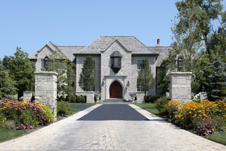 Large stone home with pillars and brick driveway Foto de archivo