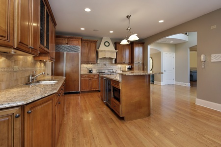 Kitchen in remodeled home with wood cabinetry photo