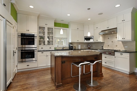 kitchen appliances: Luxury kitchen with island and white cabinetry