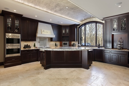 kitchen cabinets: Large kitchen in luxury home with dark wood cabinetry