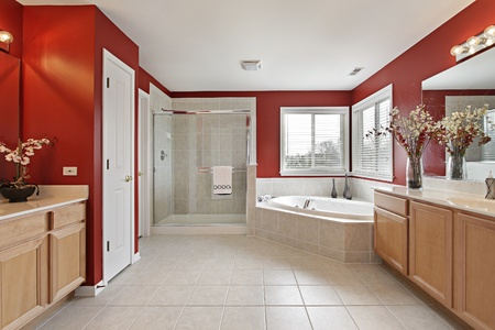 Large master bath with red walls and glass shower