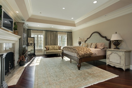 bedroom design: Master bedroom in luxury home with marble fireplace