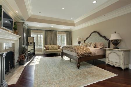 Master camera da letto in casa di lusso con camino in marmo Archivio Fotografico