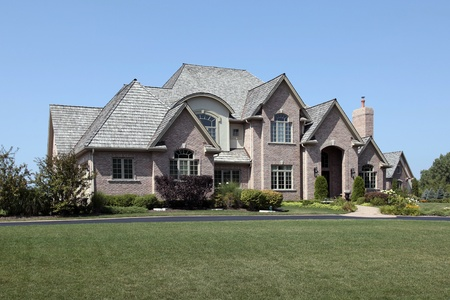 Large brick suburban home with arched entry Stock Photo