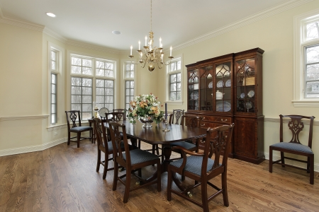 familia cenando: Comedor en hogar suburbano con paredes de color crema