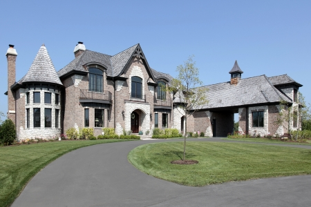 driveways: Large suburban brick and stone home with circular driveway Stock Photo