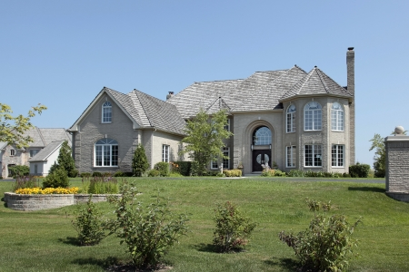 Large suburban white brick home with circular living room