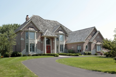 custom home: Large suburban brick and stone home with red door
