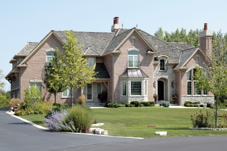 Large suburban brick and stone home with arched entry