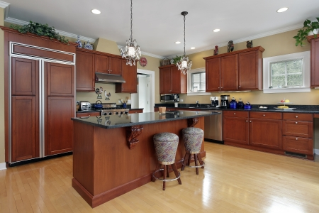 Kitchen in luxury home with cherrywood cabinetry Foto de archivo