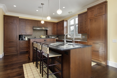 Kitchen in luxury home with oak wood cabinetry photo
