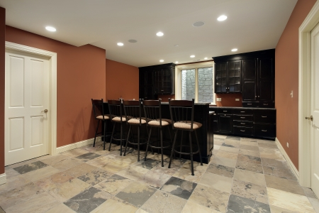 basement: Bar in basement of luxury home with dark wood cabinetry