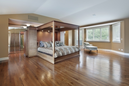 upscale: Large master bedroom with wood framed bed Editorial