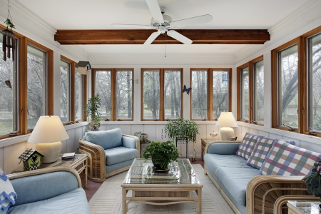 sunroom: Sunroom with wood ceiling beam and wicker furniture Editorial