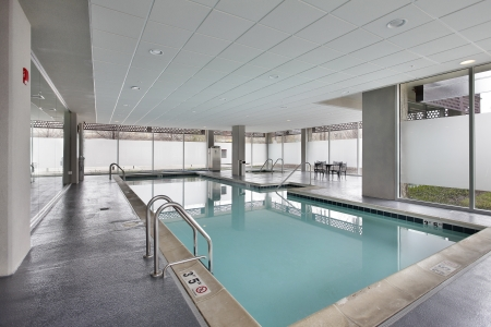 Swimming pool in condominium building with table and chairs