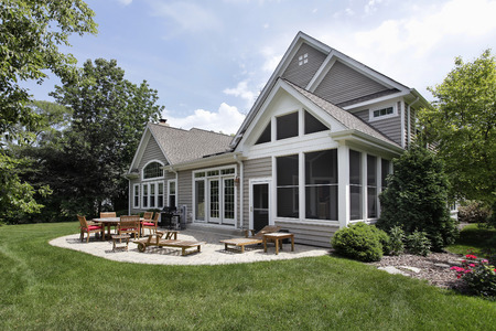 Rear view of luxury home with brick patio photo