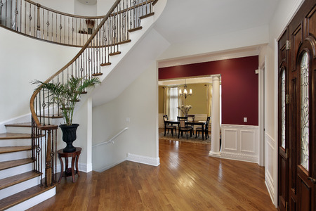 Foyer in luxury home with curved staircase and view into dining room