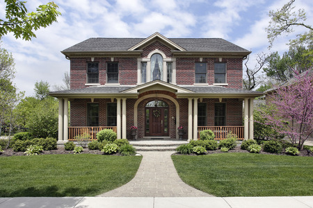costly: Brick home with white columns and arched entry