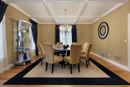Dining room with tan walls and blue drapes