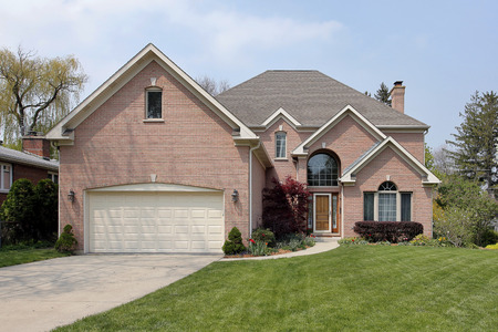 Suburban brick home with arched window above entry Foto de archivo
