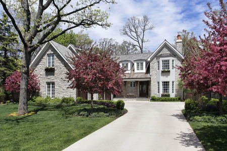 Stone home in suburbs with flowering trees 스톡 콘텐츠