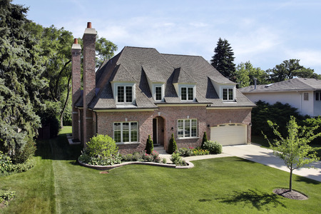 exterior architecture: Brick suburban home with arched entry