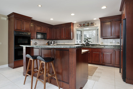 granite kitchen: Kitchen with cherry wood cabinetry and center island Stock Photo