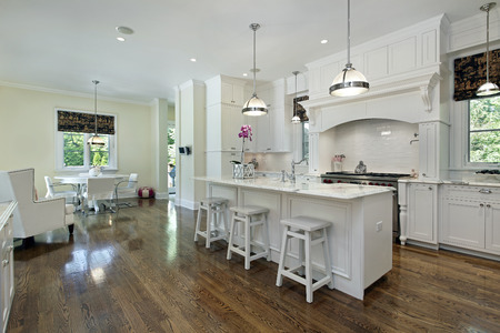 Large kitchen in luxury home with white cabinetry