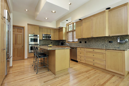 Kitchen with island and oak wood cabinetry Stock Photo