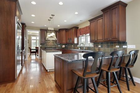 Kitchen with island and dark tile backsplash